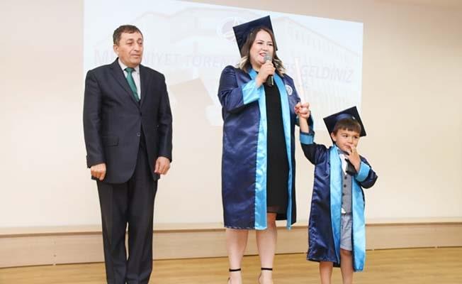 Okul birincisi diplomasını minik oğluyla birlikte aldı